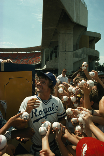 Young fans hold up baseballs for Royals star George Brett to sign.